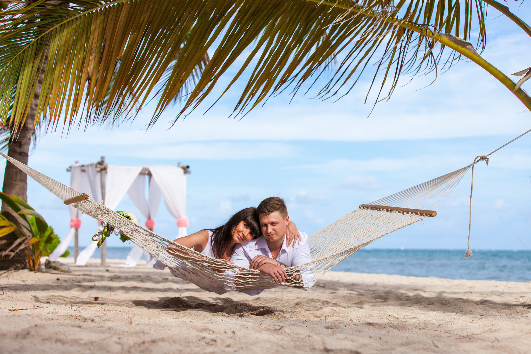 young loving couple on their wedding day, relaxing in beach hammock, outdoor beach wedding in tropics